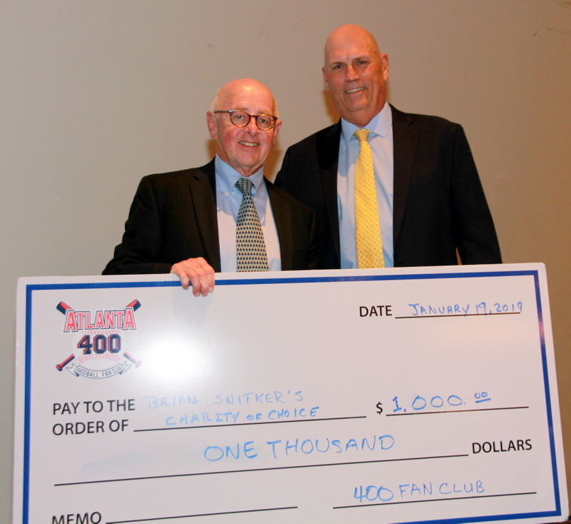 Howard Evans presents Brian Snitker with a check for his favorite charity